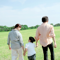 草原を手をつないで歩く家族