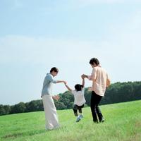 草原で手をつないで遊ぶ家族
