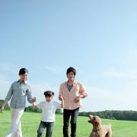 草原を手をつないで歩く親子と犬