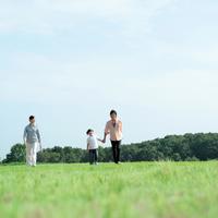 草原を手をつないで歩く親子