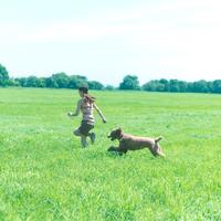 草原を走る女性と犬