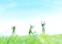 草原でジャンプする3人の女性