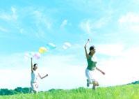 風船を持って駆ける2人の女性 20027001666| 写真素材・ストックフォト・画像・イラスト素材|アマナイメージズ