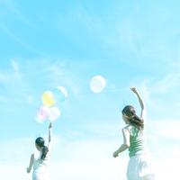 風船を持って駆ける2人の女性