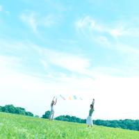 風船を持って草原に立つ2人の女性