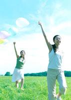 風船を持って草原を歩く2人の女性