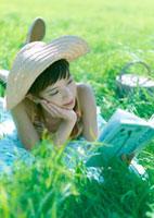 草原に寝転び読書している女性