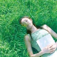 草原に寝転び目を閉じている女性