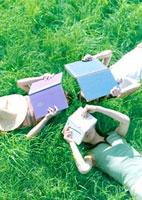 草原に寝転び読書する3人の女性