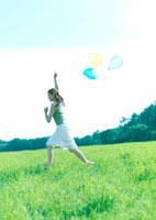 風船を持って草原を駆ける女性