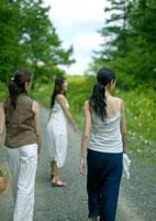 一本道を散歩する3人の女性