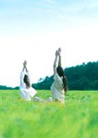 草原でヨガをする2人の女性