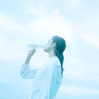 空と水を飲む女性