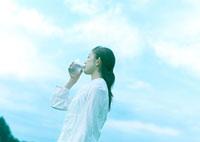 空と水を飲む女性 20027001866| 写真素材・ストックフォト・画像・イラスト素材|アマナイメージズ