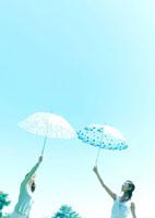傘を高く上げる2人の女性