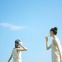 糸電話をする2人の女性