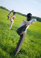 草原でヨガをする3人の女性