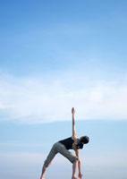 空とヨガをする女性