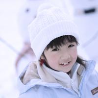 雪だるまの前で微笑む女の子 20027002055| 写真素材・ストックフォト・画像・イラスト素材|アマナイメージズ