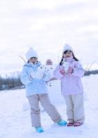 雪だるまを持つ2人の女の子 20027002056| 写真素材・ストックフォト・画像・イラスト素材|アマナイメージズ