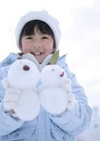 2つの雪だるまを持つ女の子 20027002058| 写真素材・ストックフォト・画像・イラスト素材|アマナイメージズ