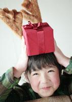 頭の上にプレゼントを乗せた女の子 20027002131A| 写真素材・ストックフォト・画像・イラスト素材|アマナイメージズ