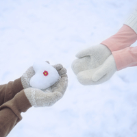 雪で作ったハートを渡すカップルの手元