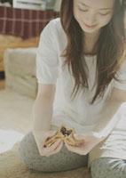 たいやきを半分に割る女性 20027002321| 写真素材・ストックフォト・画像・イラスト素材|アマナイメージズ