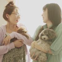 子犬を抱いて微笑み合う二人の女性