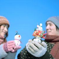 門松と雪ダルマを持つカップル