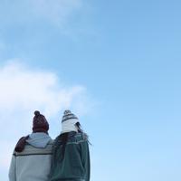 青空の下、寄り添うカップルの後ろ姿