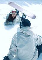 スノーボードで転んだ女性と男性 20027003023| 写真素材・ストックフォト・画像・イラスト素材|アマナイメージズ