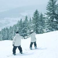 スノーボードをするカップルの後姿