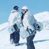 スノーボードを持って歩くカップル