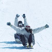 スノーボードの上に座って滑るカップル 20027003047| 写真素材・ストックフォト・画像・イラスト素材|アマナイメージズ