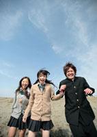 砂浜を走る3人の高校生