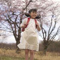 桜の前でジャンプする女の子
