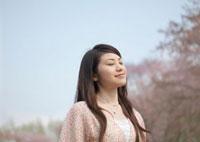桜の前で目を閉じる女性 20027003423| 写真素材・ストックフォト・画像・イラスト素材|アマナイメージズ