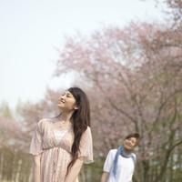 桜の前で微笑む2人の女性