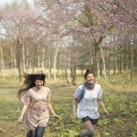 桜の前を走る2人の女性