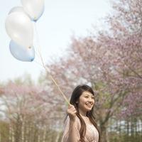 桜の前で風船を持つ女性