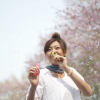 桜の前でシャボン玉をする女性