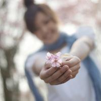 桜の花を差し出す女性
