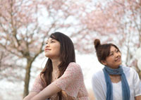 桜の下で微笑む2人の女性