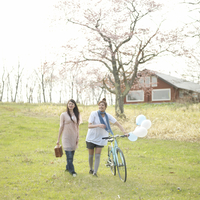 桜の前を歩く2人の女性