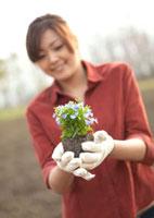 花の苗を持つ女性