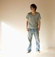 壁の前に立つ20代の男性