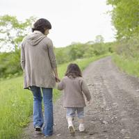 森の一本道を手をつないで歩く親子