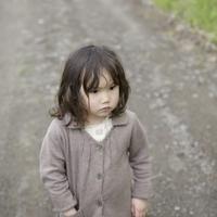 森の一本道に佇む女の子