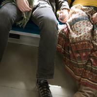 地図を見ながら電車で一人旅をする女性